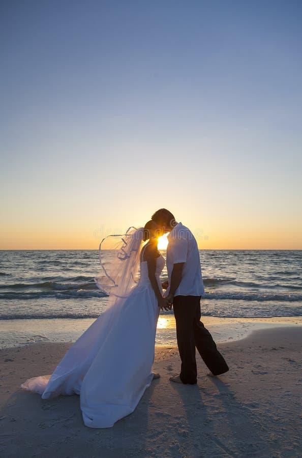 Państwa Młodzi małżeństwa całowania zmierzchu Plażowy ślub zdjęcia royalty free