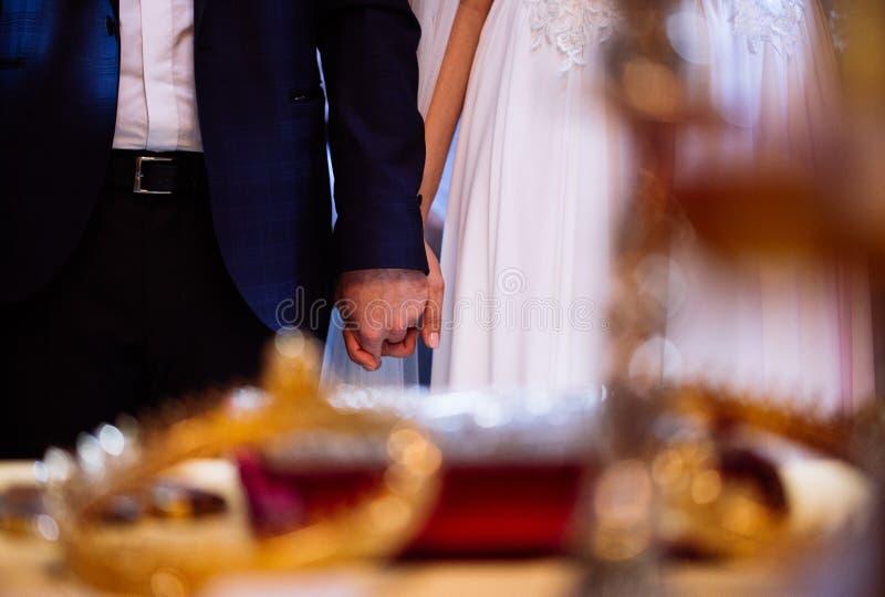 Państwa młodzi mienia ręki podczas ślubnej kościelnej ceremonii obrazy stock