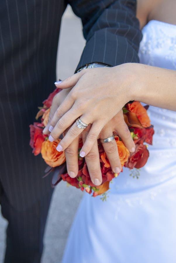 Państwa młodzi ręki, pierścionki i bukiet, obraz royalty free