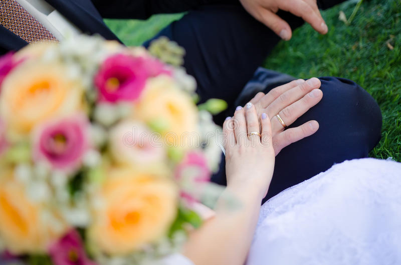 Państwa młodzi ` s trzyma each inną ` s rękę z obrączkami ślubnymi zdjęcia royalty free