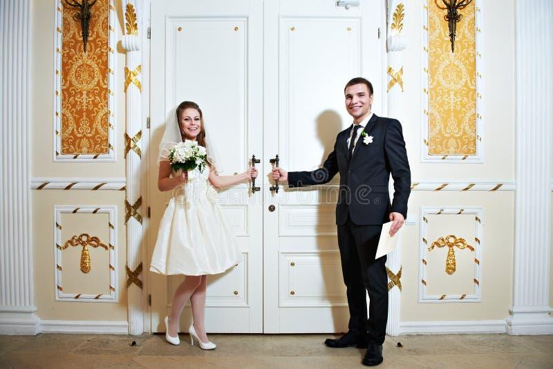 Państwo młodzi blisko drzwi ślubna sala zdjęcia royalty free