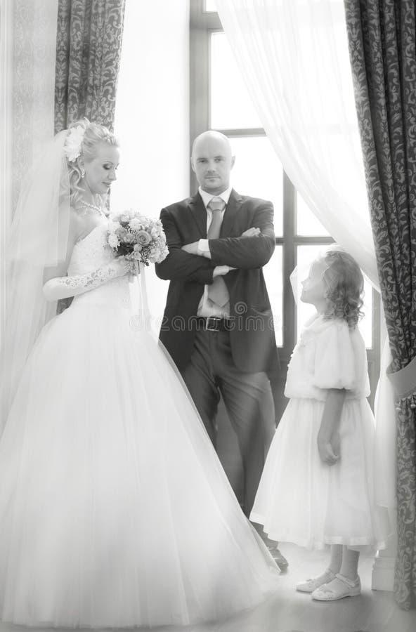 Państwo młodzi i mała dziewczynka przy ślubem obrazy stock