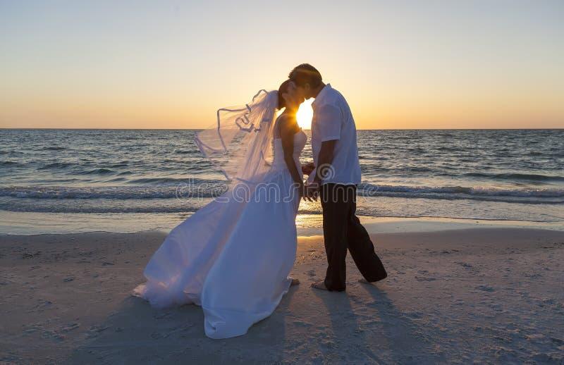 Państwo Młodzi pary małżeńskiej zmierzchu Plażowy ślub obrazy stock