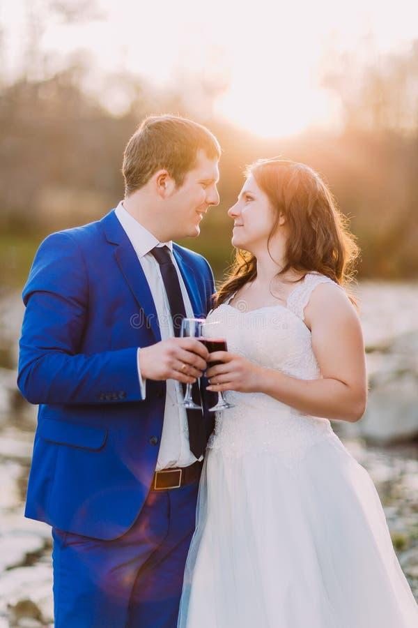 Państwo młodzi pije czerwone wino trzyma szklanego macanie each inny Błyszczący słońce przy tłem obraz stock