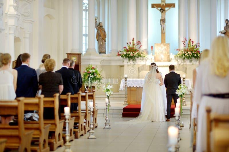 Państwo młodzi przy kościół podczas ślubu zdjęcie stock