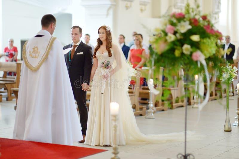 Państwo młodzi przy kościół podczas ślubu fotografia stock