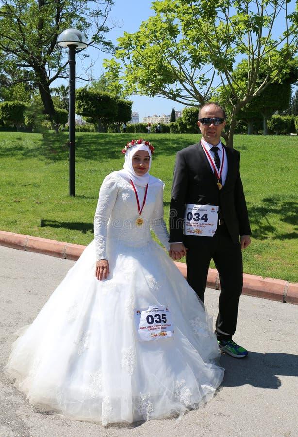 Państwo Młodzi przygotowywający dla maratonu z kostiumem przy Pomarańczowym okwitnięcie karnawałem zdjęcia royalty free