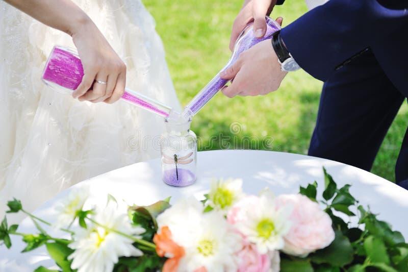 Państwo młodzi robi piasek ceremonii podczas ślubu zdjęcia stock