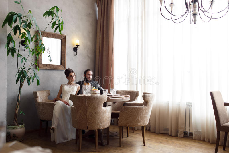 Państwo młodzi siedzi w karłach przy stołem w pięknej jaskrawej sala zdjęcia royalty free