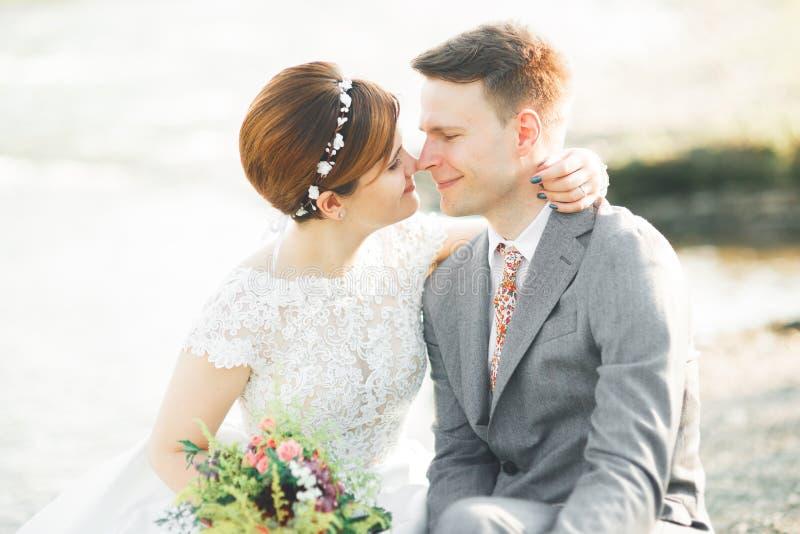 Państwo młodzi trzyma pięknego ślubnego bukiet Pozować blisko rzeki obraz royalty free