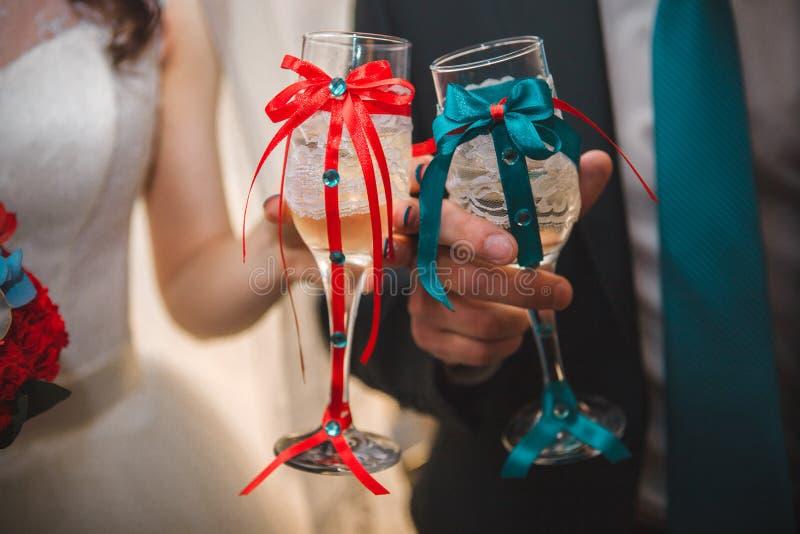 Państwo młodzi trzyma szkła szampan panny młodej ceremonii kwiatu ślub Szampańscy szkła dekorujący z faborkami w górę fotografia royalty free