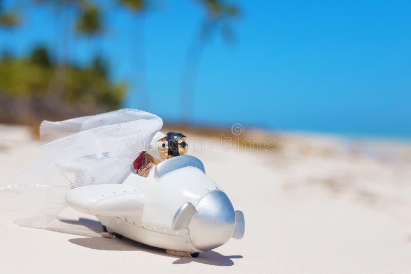 Państwo młodzi w małym ślubu samolotu modelu na plaży fotografia royalty free