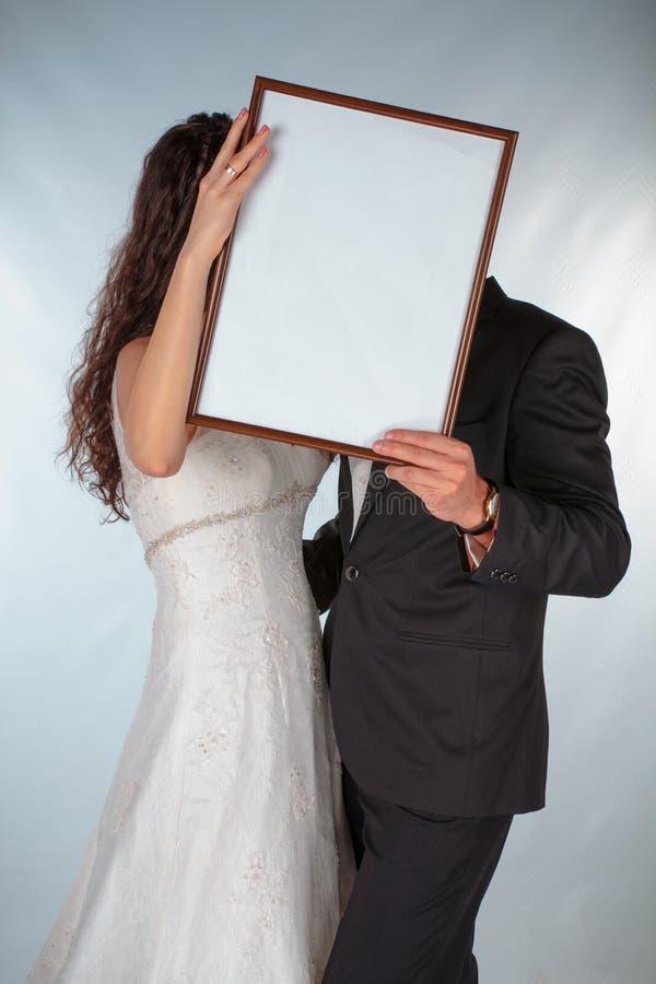 Państwo młodzi z ramą dla fotografii royalty ilustracja