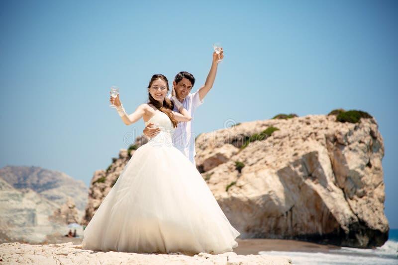 Państwo młodzi z szkłami szampan na plażowym morzu śródziemnomorskim zdjęcia stock