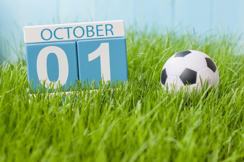Października 1st dzień 1 miesiąc, koloru kalendarz na zielonej trawy tle z piłką Jesień czas Futbolu i piłki nożnej sztuka obrazy royalty free