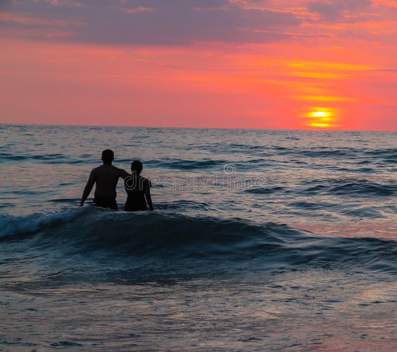 Paar-überwachender Sonnenuntergang am Strand stockfotos