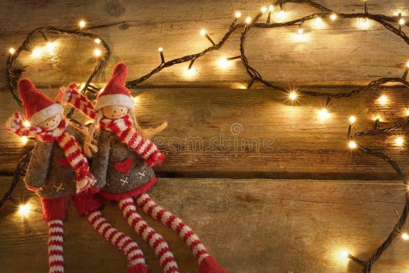 Paar aanbiddelijke en leuke Kerstmiself die in rustieke houten lijst met gele Kerstmislichten zitten Met exemplaarruimte stock afbeeldingen