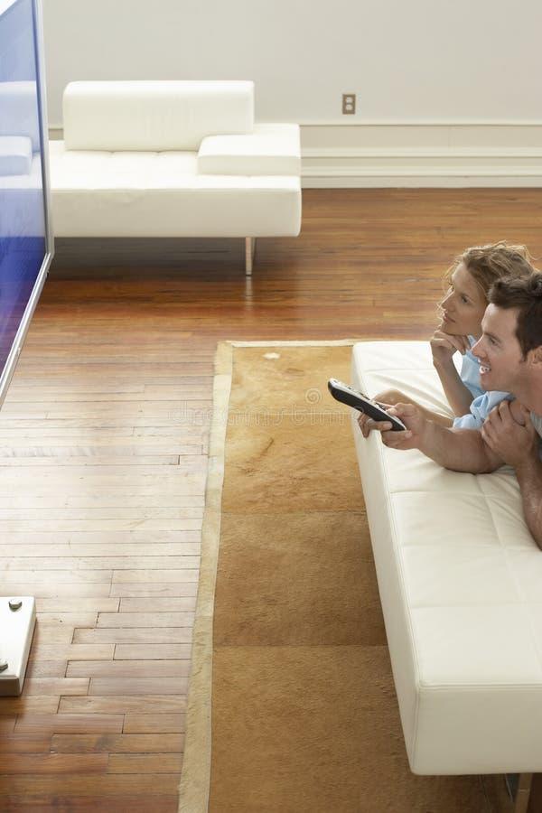 Paar-aufpassender Plasmafernseher zu Hause lizenzfreie stockfotos