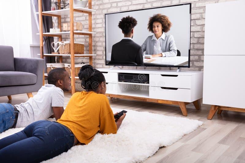 Paar-aufpassendes Fernsehen zu Hause stockfotografie