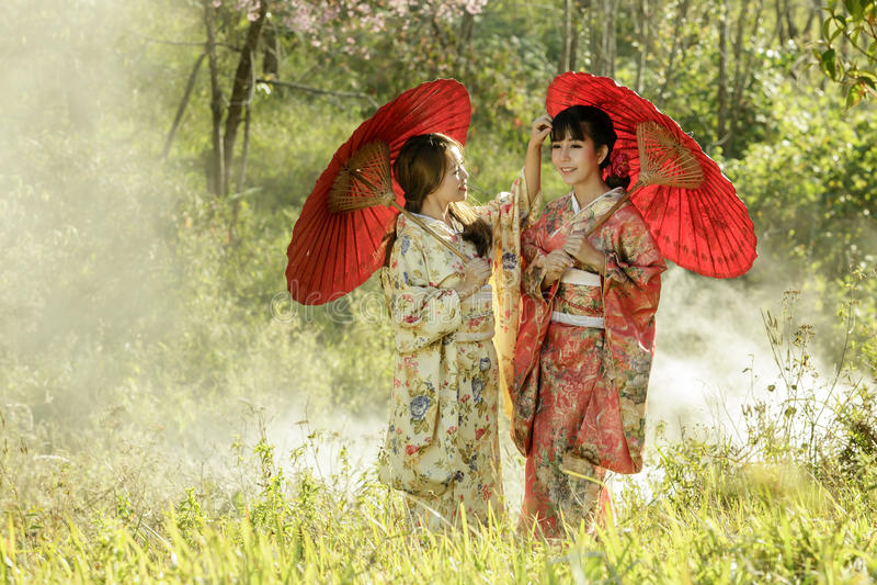 Paar Aziatische vrouwen die traditionele Japanse kimono en rood u dragen royalty-vrije stock foto's