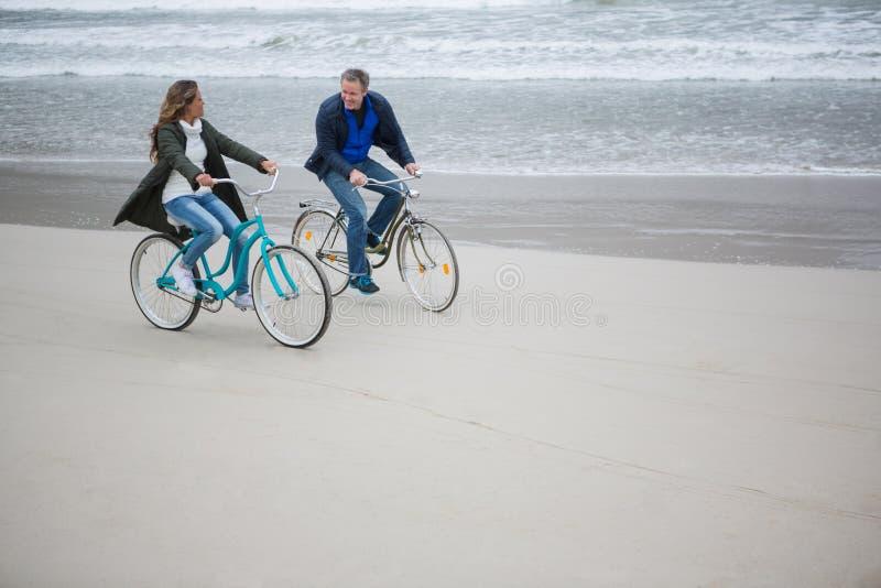 Paar berijdende fiets op strand stock foto's