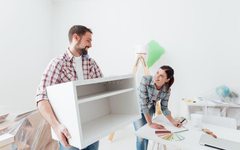 Paar bewegend meubilair in hun nieuw huis stock fotografie