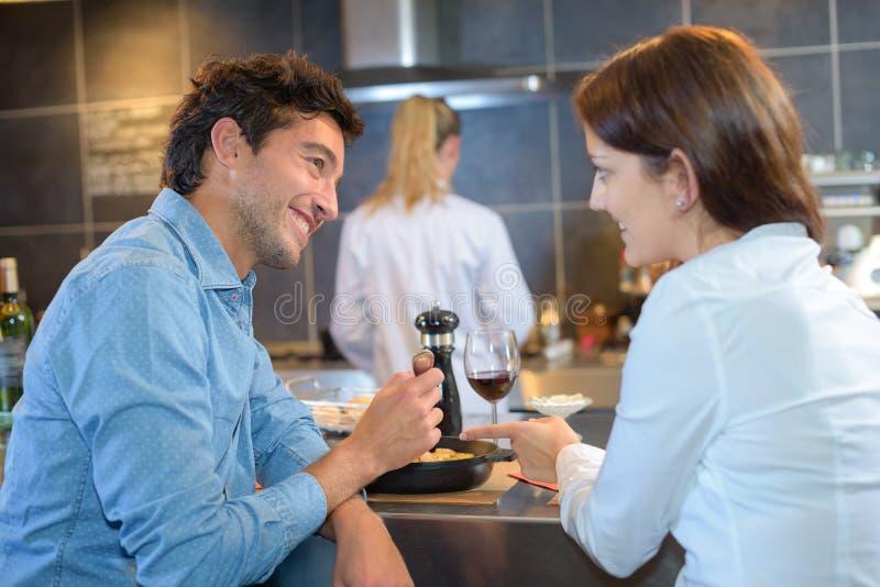 Paar bij bar het eten wordt gezeten die royalty-vrije stock foto's