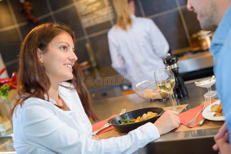 Paar bij bar wordt gezeten die maaltijd eten die royalty-vrije stock fotografie