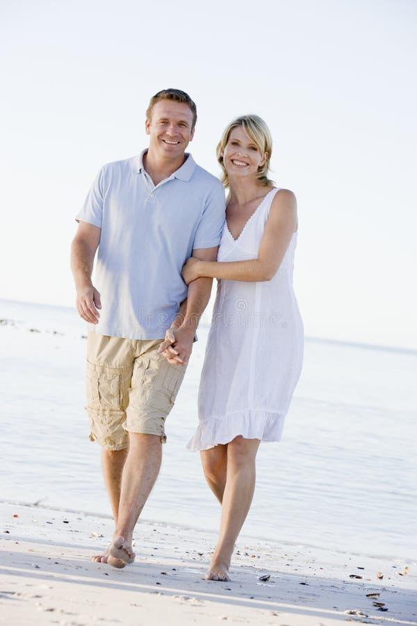 Paar bij de strandholding handen en het glimlachen