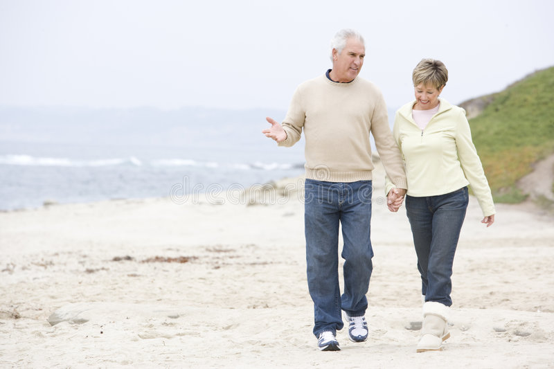 Paar bij de strandholding handen en het glimlachen stock fotografie