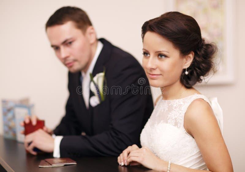 Paar bij een ontvangstbureau met hun paspoorten stock fotografie