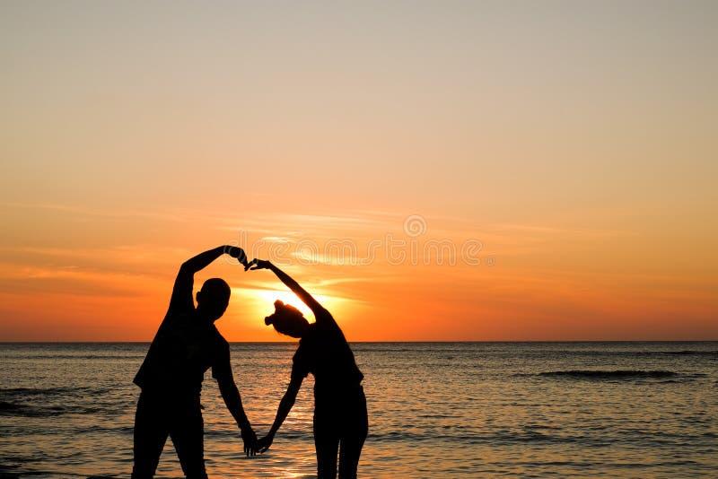 Paar bij gouden zonsondergang bij strand stock afbeeldingen