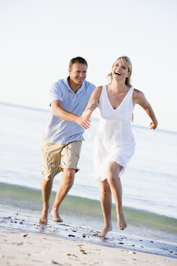 Paar bij het en strand dat speelt glimlacht stock fotografie