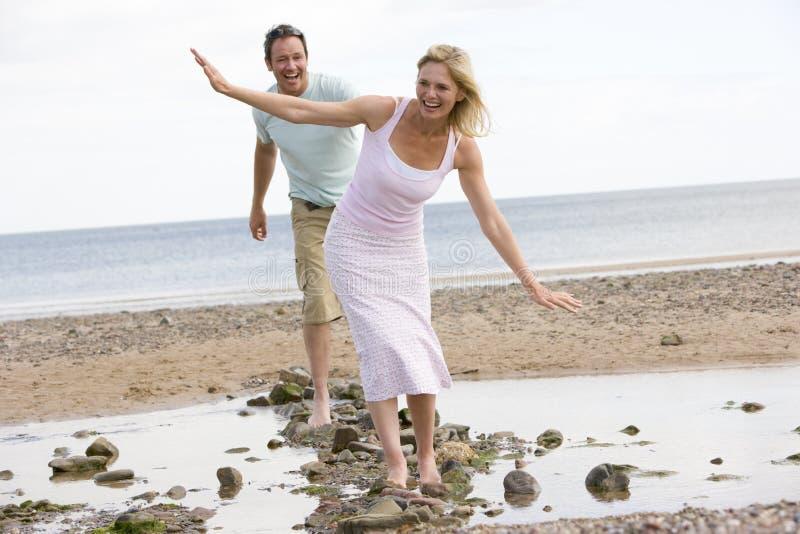 Paar bij het strand dat bij stenen en het glimlachen loopt royalty-vrije stock afbeeldingen