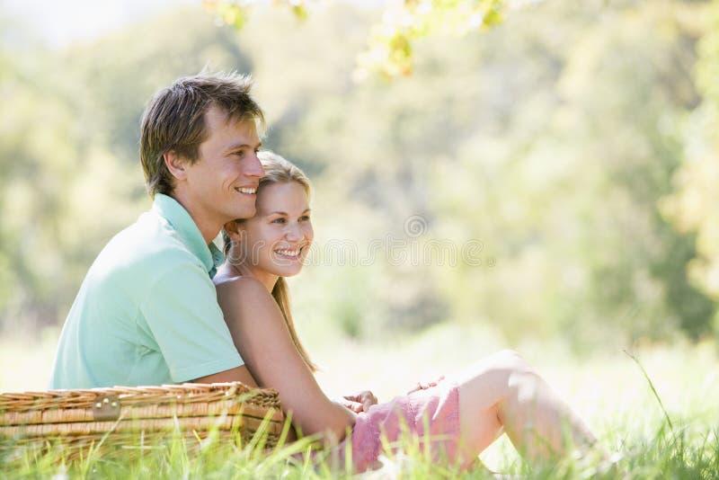 Paar bij park dat een picknick en het glimlachen heeft stock afbeeldingen