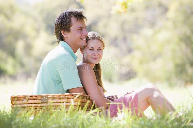 Paar bij park dat een picknick en het glimlachen heeft royalty-vrije stock afbeelding