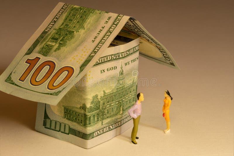Paar bij voorzijde van het huis van honderd dollarsrekeningen die wordt gemaakt Onroerende goederenuitgaven die hypotheek en bezi royalty-vrije stock afbeelding