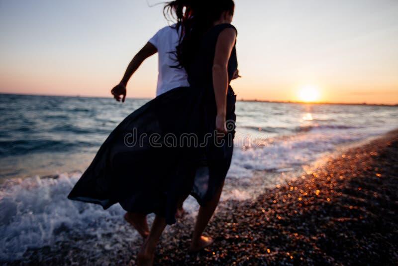 Paar bij zonsondergang door het overzees stock foto