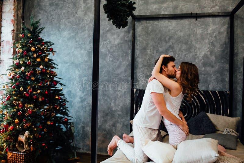 Paar binnen in pyjama's die op het bed dichtbij de Kerstboom rusten royalty-vrije stock foto's