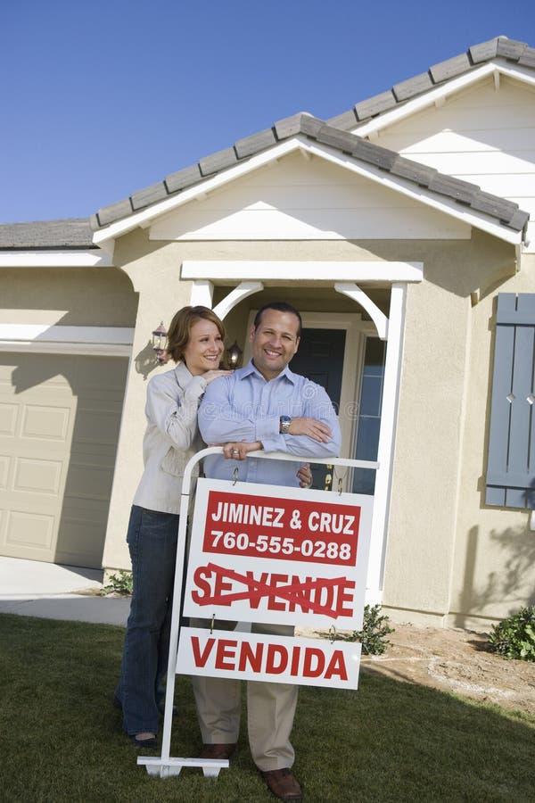 Paar buiten Huis met Verkocht Teken stock afbeeldingen
