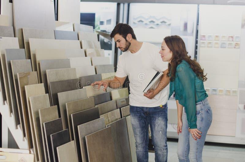 Paar ceramisch en tegels die voor hun nieuwe huisvloer kijken stock afbeelding
