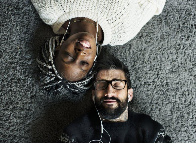 Paar dat aan muziek samen luistert stock afbeelding