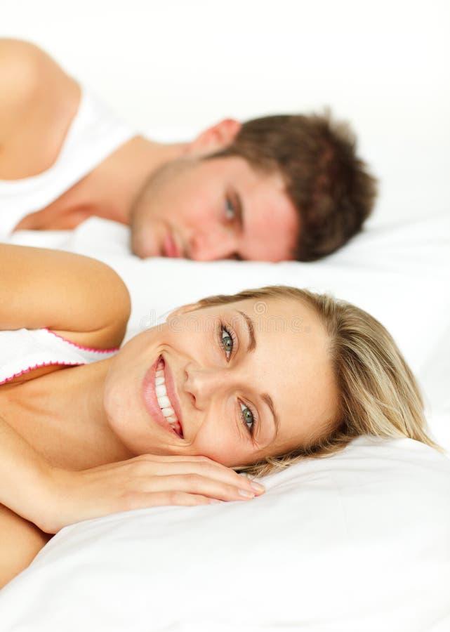 Paar dat in bed en vrouwen het glimlachen rust stock fotografie