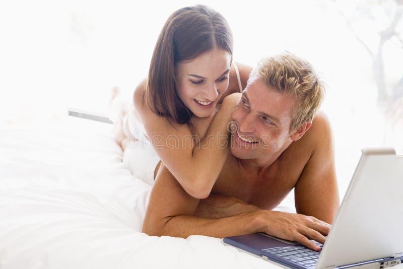 Paar dat in bed met laptop het glimlachen ligt stock foto's