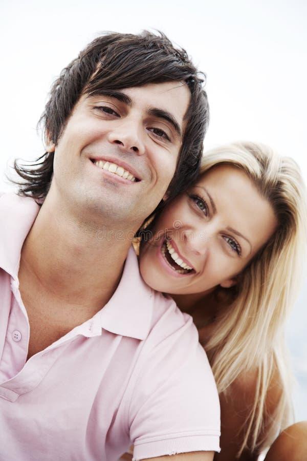 Paar dat bij camera glimlacht stock afbeeldingen