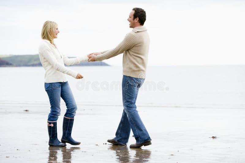 Paar dat bij de handen van de strandholding het glimlachen loopt stock foto's