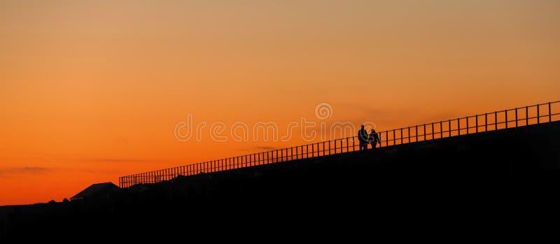 Paar dat bij zonsondergang loopt royalty-vrije stock afbeelding