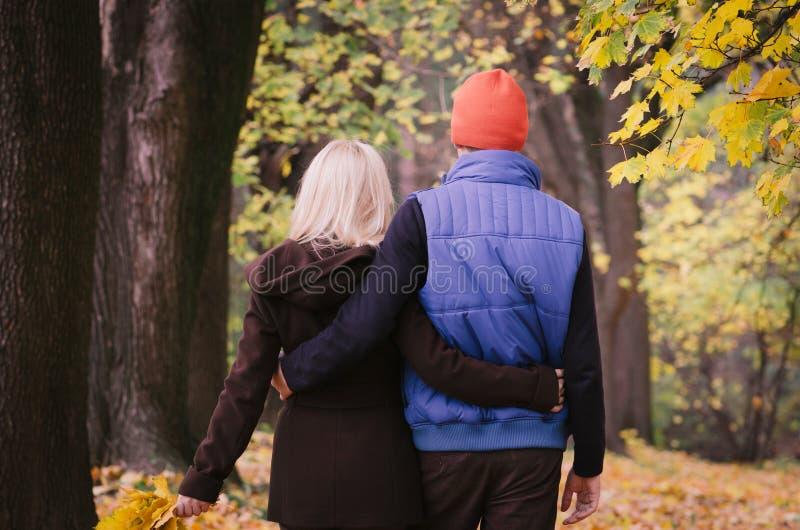 Paar dat in de herfstpark loopt stock foto's