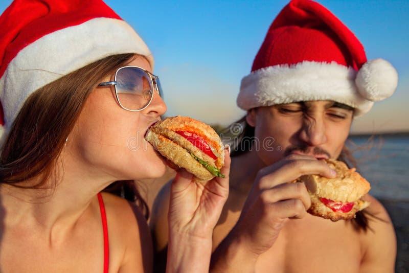 Paar dat in de hoeden van de Kerstman een snel voedselhamburger eet stock foto's