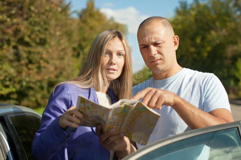 Paar dat de kaart op de weg bekijkt royalty-vrije stock afbeelding